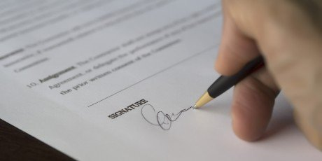 A close-up of a hand holding a black pen, whilst signing their signature on the bottom of an insurance document