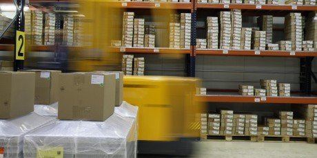 A warehouse filled with boxes stacked on racking, and a yellow forklift that is blurry because it is moving