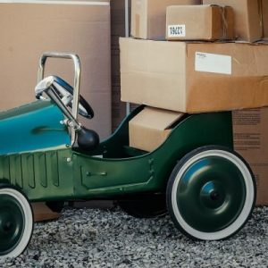 A green toy car with cardboard boxes stacked on the back